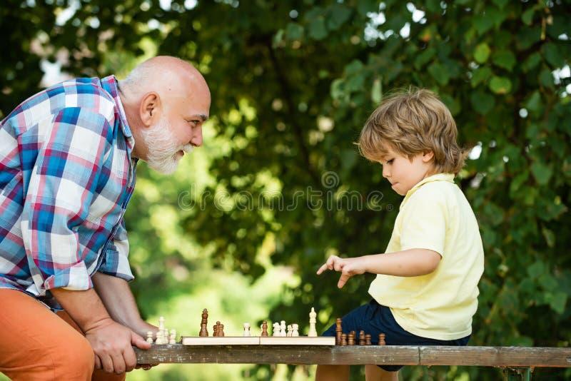El abuelo y el nieto hermosos están jugando a ajedrez mientras que pasa el tiempo junto Niño pequeño que juega a ajedrez con su fotografía de archivo libre de regalías