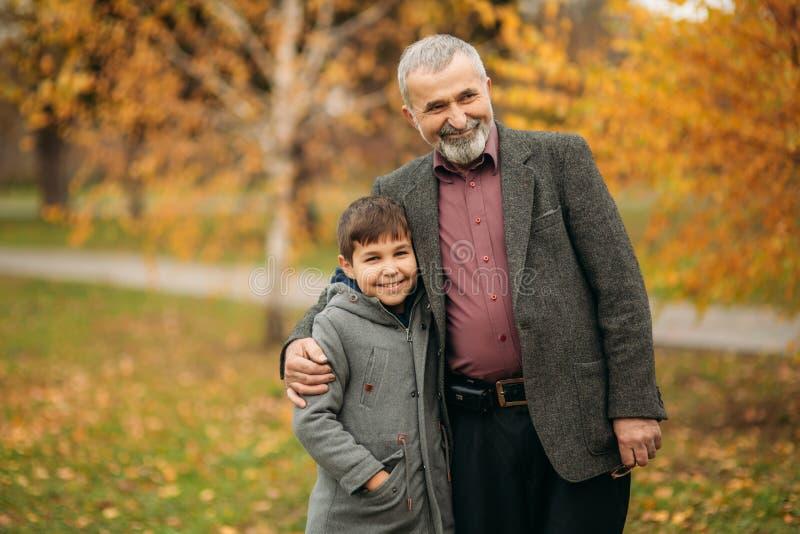 El abuelo y el nieto pasan tiempo en parque del otoño Se abrazan y caminan Tiempo de Fmily imagen de archivo libre de regalías