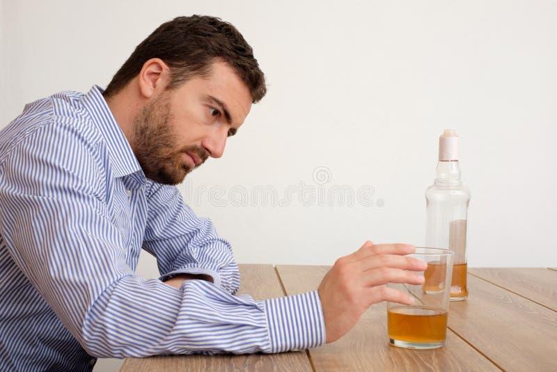 El abusar deprimido del hombre del alcohol que intenta olvidar sus problemas fotos de archivo