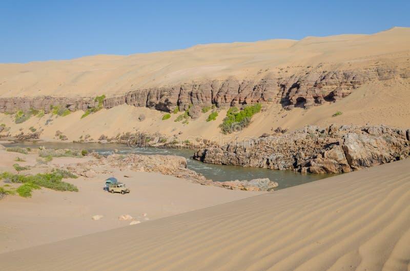 El acampar campo a través en el río de Kunene delante de las dunas de arena antiguas elevadas del desierto de Namib de Namibia y  imagen de archivo libre de regalías