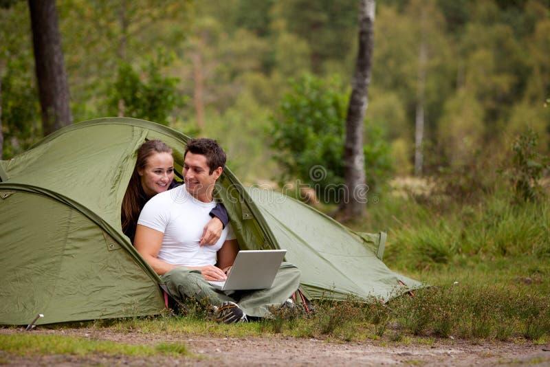 El acampar con el ordenador imagen de archivo libre de regalías
