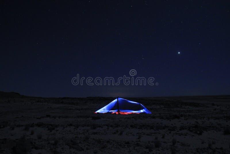 El acampar con la tienda que brilla intensamente y el cielo estrellado en Namibia imagenes de archivo