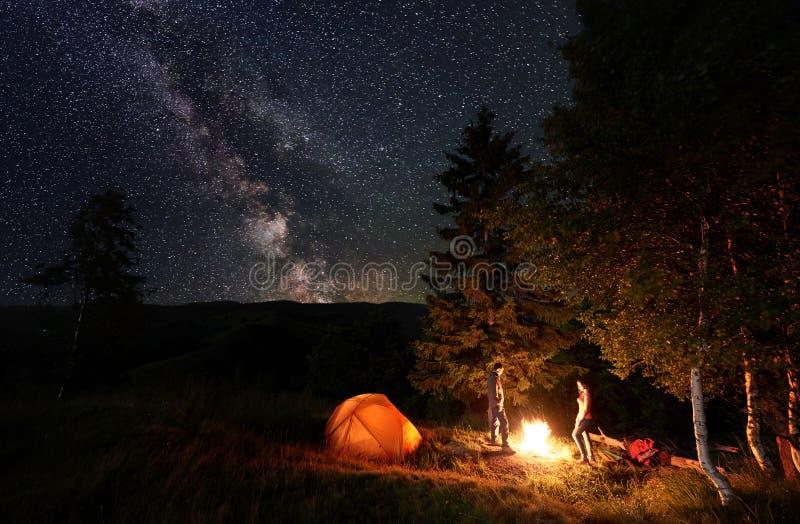 El acampar de la noche Fuego que hace una pausa del individuo y de la muchacha cerca del bosque y de las tiendas debajo del cielo imagenes de archivo