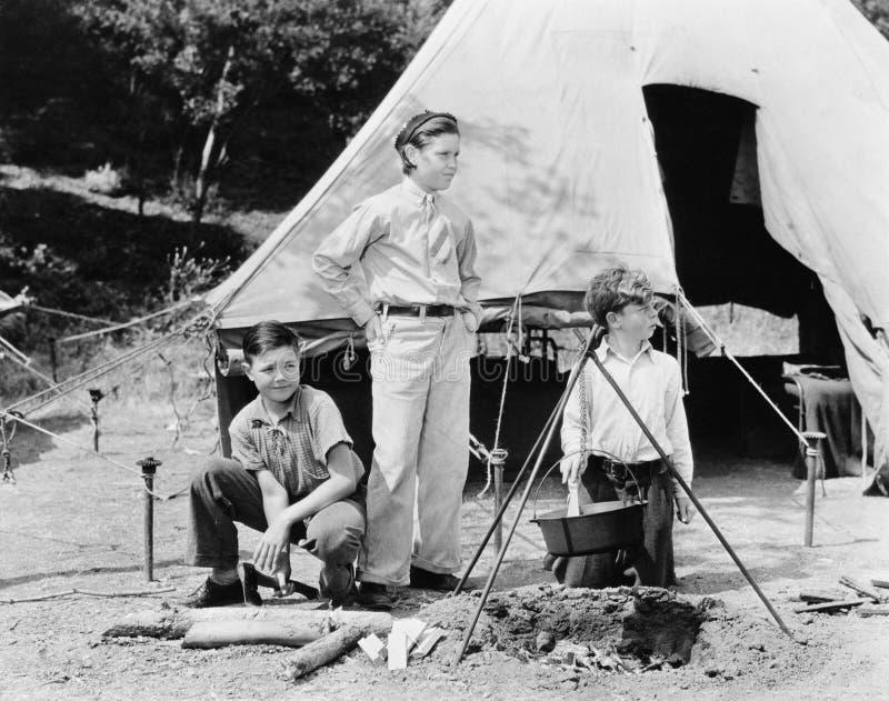 El acampar de tres muchachos (todas las personas representadas no son vivas más largo y ningún estado existe Garantías del provee fotografía de archivo libre de regalías