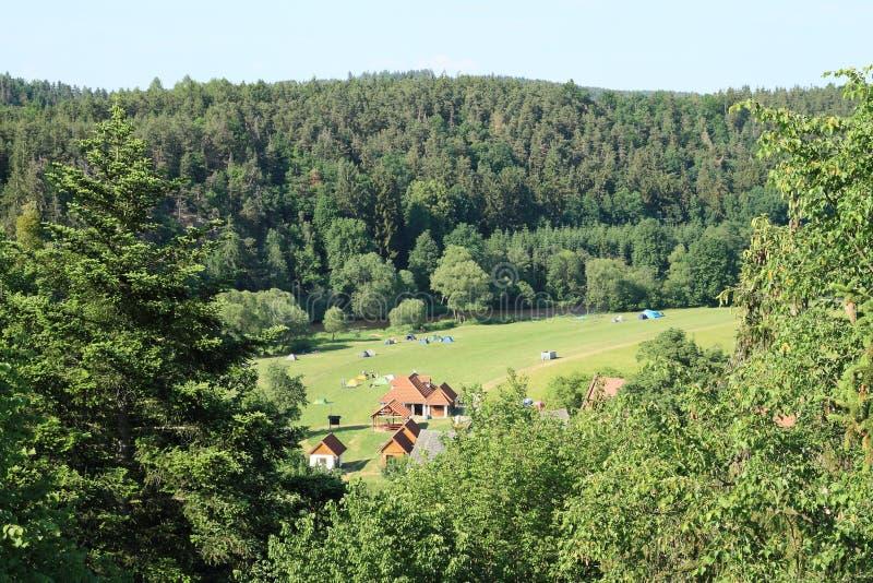 El acampar en prado entre bosques fotos de archivo