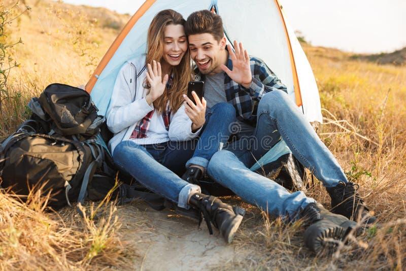 El acampar joven alegre de los pares, sentándose imagenes de archivo