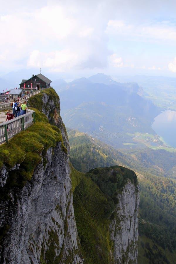 El acantilado con la opinión sobre las montañas y un lago en las nubes fotos de archivo