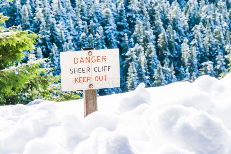 El acantilado escarpado del peligro evita la muestra al borde de la cubierta de tierra con nieve imágenes de archivo libres de regalías