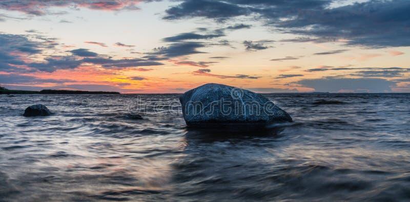 El acantilado y la playa del mar se encendieron por el sol poniente, imagen de archivo libre de regalías
