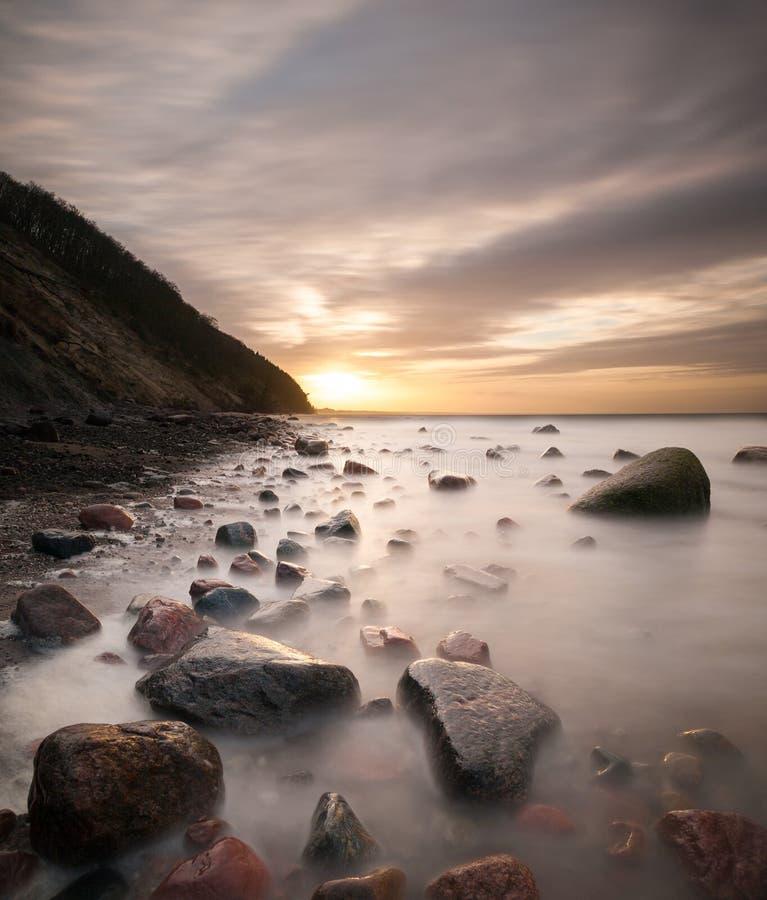 El acantilado y la playa del mar se encendieron por el sol poniente, imagen de archivo