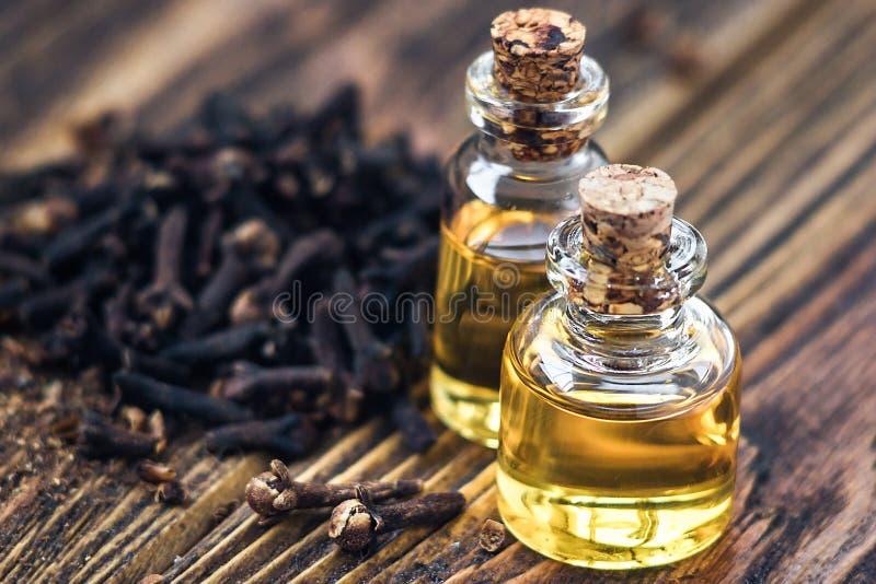 El aceite esencial en la botella de cristal y los clavos secos en copia de madera oscura del fondo espacian el tratamiento de la  fotografía de archivo libre de regalías