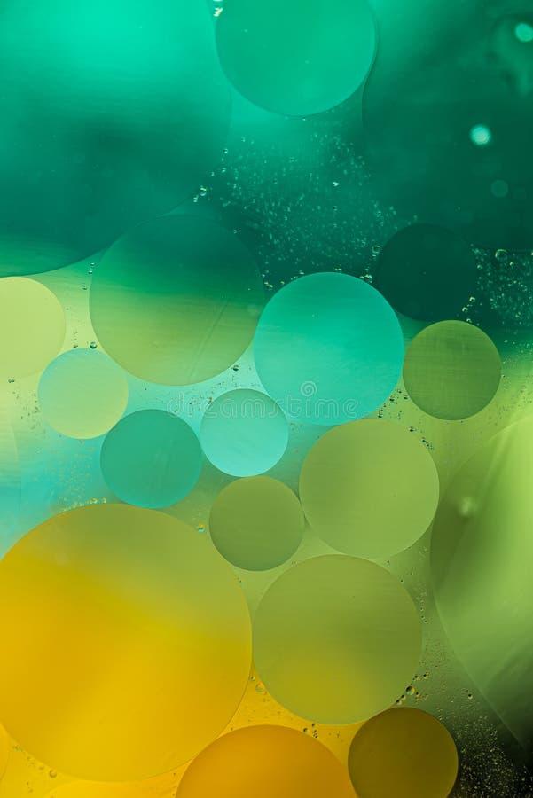El aceite verde, amarillo de la pendiente cae en el agua - fondo abstracto imagenes de archivo