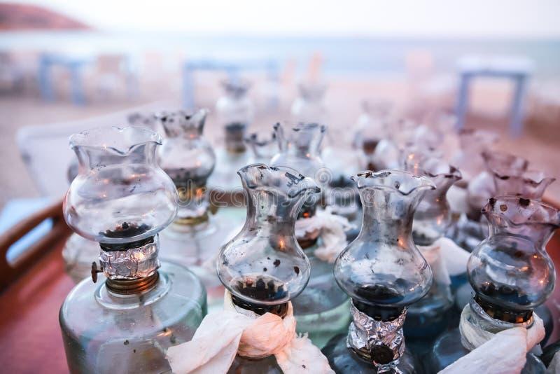 El aceite viejo que las lámparas de cristal con arreglos de DIY recolectaron en la tabla en Griego sea foto de archivo libre de regalías