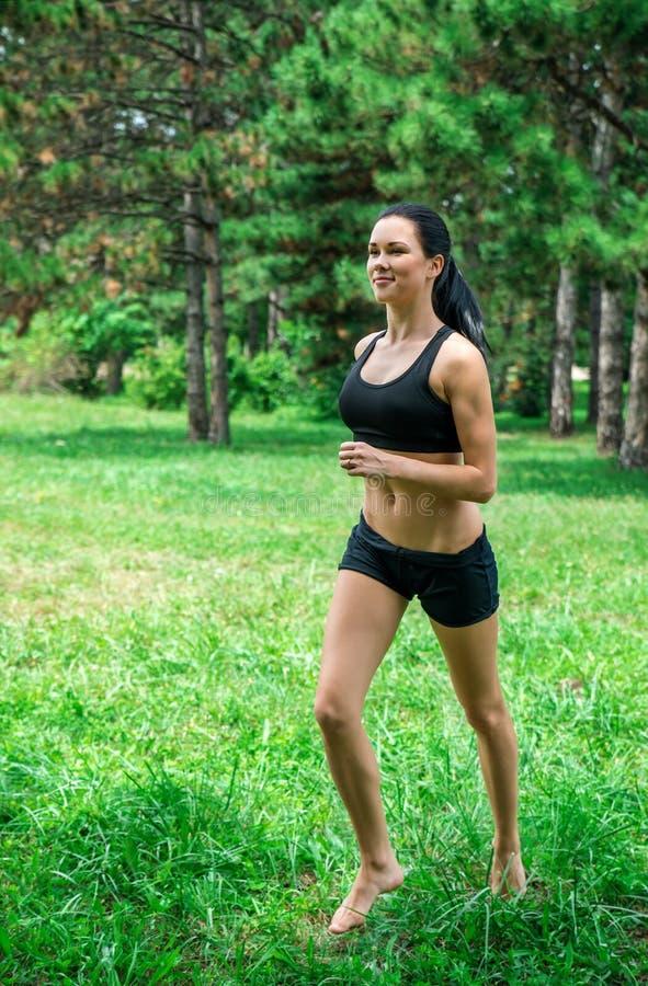 El activar femenino afuera en el parque Corredores que entrenan al aire libre foto de archivo