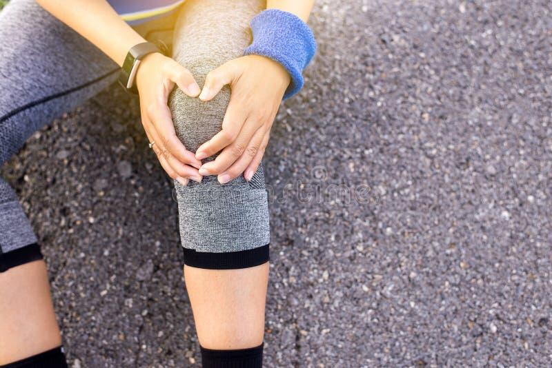 El activar y entrenamiento al aire libre, atleta que sufre de dolor en pierna y lesión de rodilla de funcionamiento después de ej foto de archivo libre de regalías