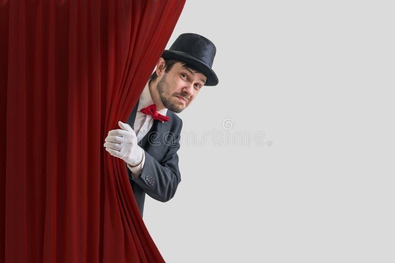 El actor o el ilusionista nervioso está ocultando detrás de la cortina roja en teatro fotografía de archivo libre de regalías