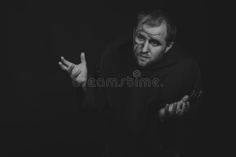 El actor so pretexto de un mendigo en un fondo oscuro fotografía de archivo libre de regalías