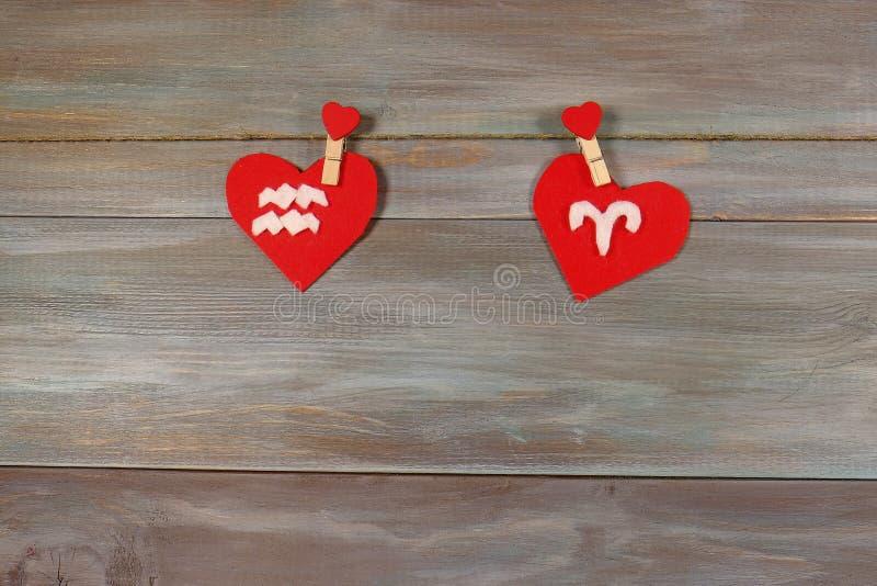 El acuario y el aries son muestras del zodiaco y del corazón CCB de madera fotografía de archivo libre de regalías