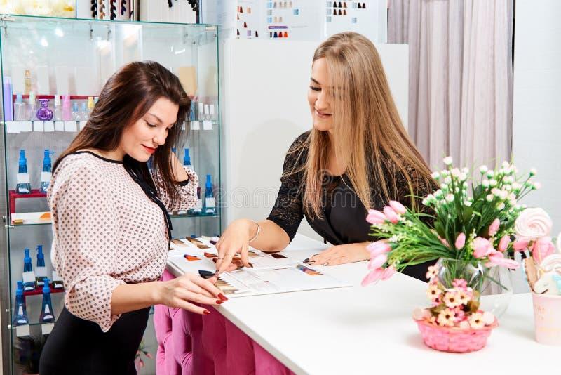 El administrador del salón de belleza dice a la muchacha al cliente sobre los servicios del salón imagenes de archivo