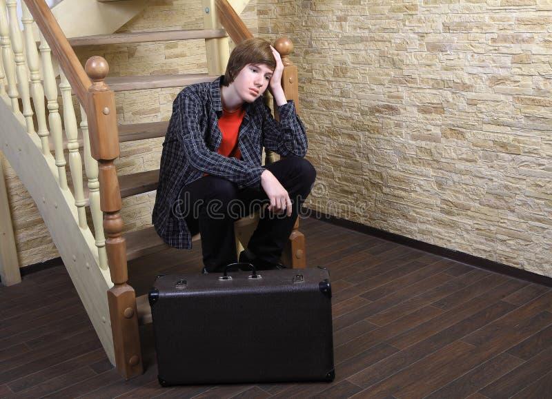 El adolescente 14 años, sentándose en las escaleras de madera acerca a la maleta. fotografía de archivo