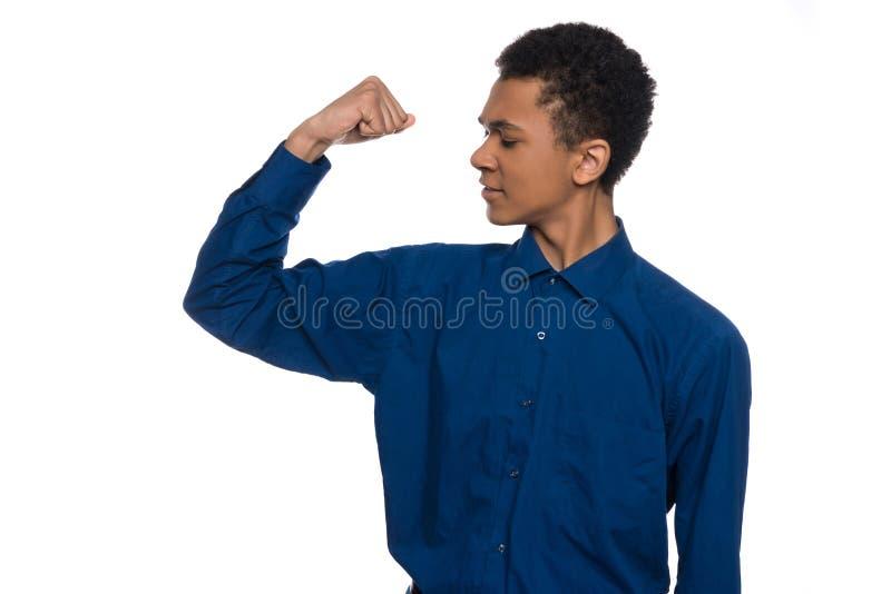 El adolescente afroamericano muestra los músculos en el brazo foto de archivo