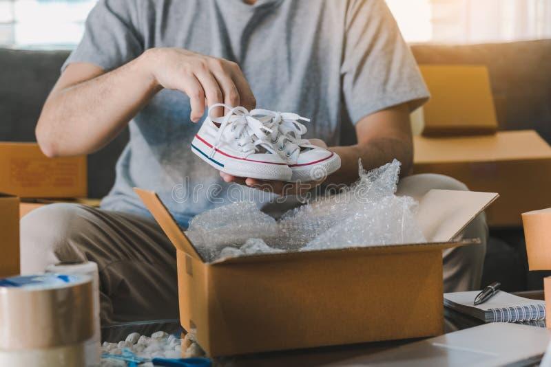 El adolescente asiático del empresario está llevando los zapatos de bebé y puesto en un cliente de la caja de cartón para entrega foto de archivo