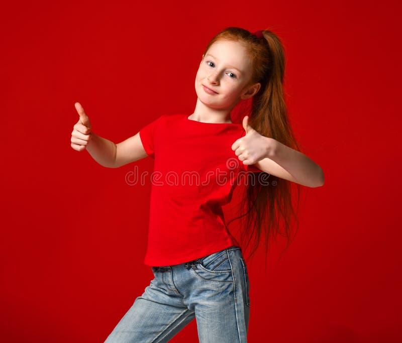 El adolescente con la piel pecosa sana, llevando una camiseta roja, mirando la c?mara muestra los pulgares grandes para arriba, e foto de archivo