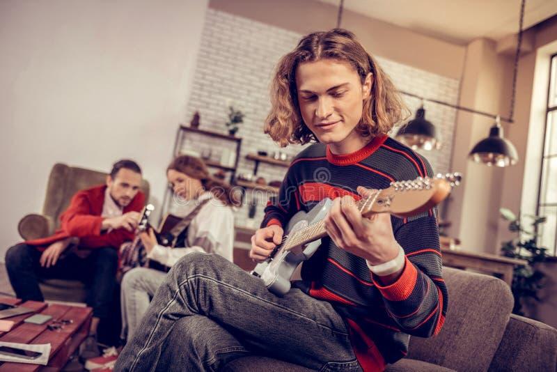 El adolescente con la sacudida cortó la sonrisa mientras que sentía música que componía alegre fotos de archivo