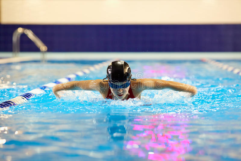 El adolescente de la muchacha del nadador en la piscina nada la mariposa dentro fotos de archivo libres de regalías