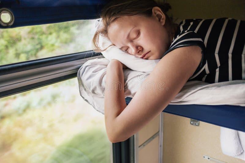 El adolescente duerme en tren foto de archivo