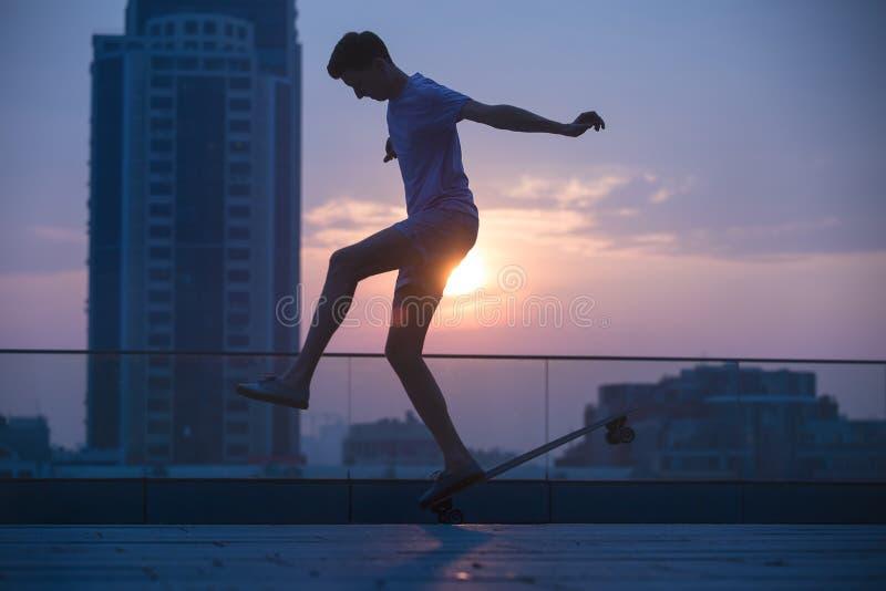 El adolescente elegante hace trucos de un longboard fotografía de archivo libre de regalías