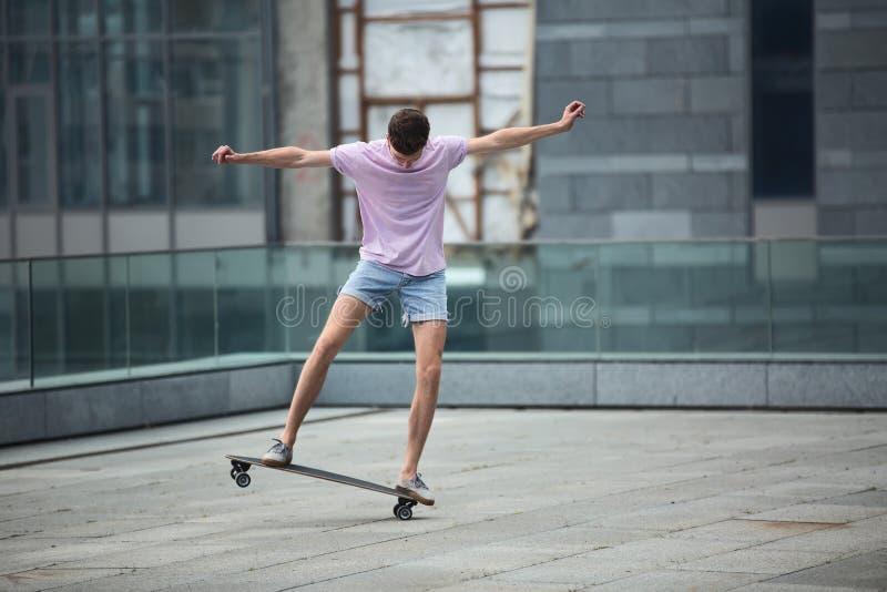 El adolescente elegante hace trucos de un longboard fotografía de archivo