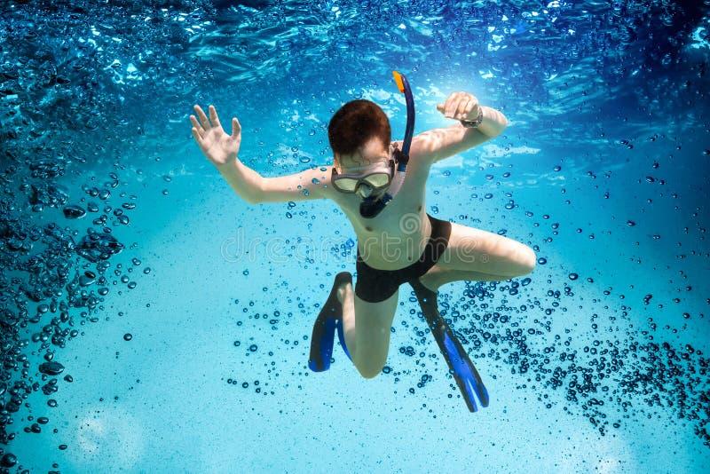 El adolescente en la máscara y el tubo respirador nadan bajo el agua. imagen de archivo