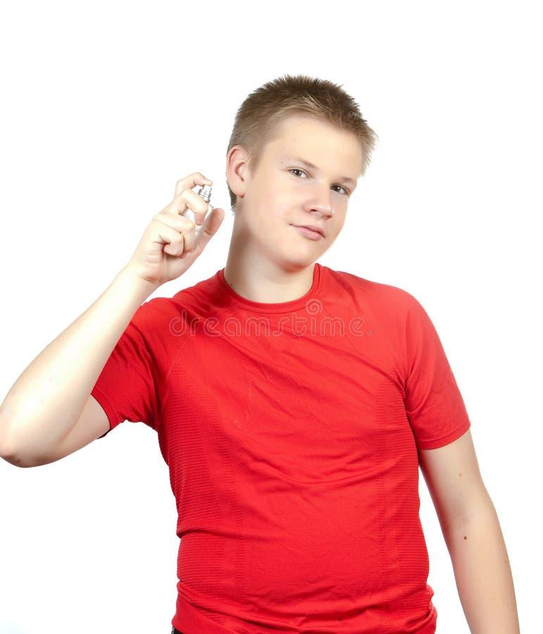 El adolescente en una camiseta roja con una botella de eau de toilette en manos imágenes de archivo libres de regalías