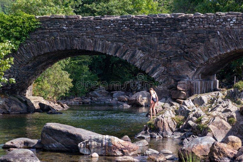El adolescente está entrando en el río Duddon por el viejo brid de piedra imagen de archivo