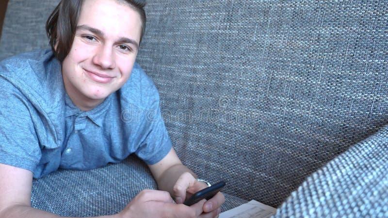 El adolescente hermoso del muchacho que habla en el teléfono se sienta en un sofá gris imágenes de archivo libres de regalías