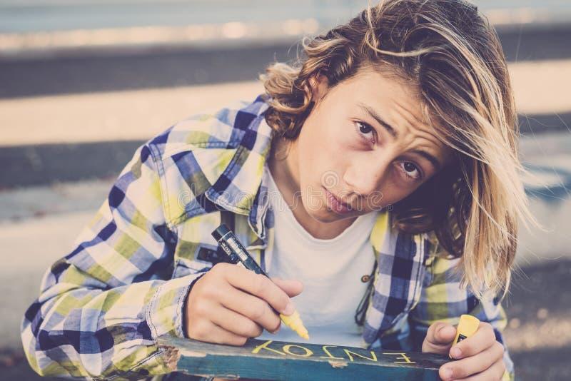 El adolescente joven hermoso del muchacho con la camisa de moda larga del pelo rubio escribir goza en un pedazo de madera recicla imagen de archivo
