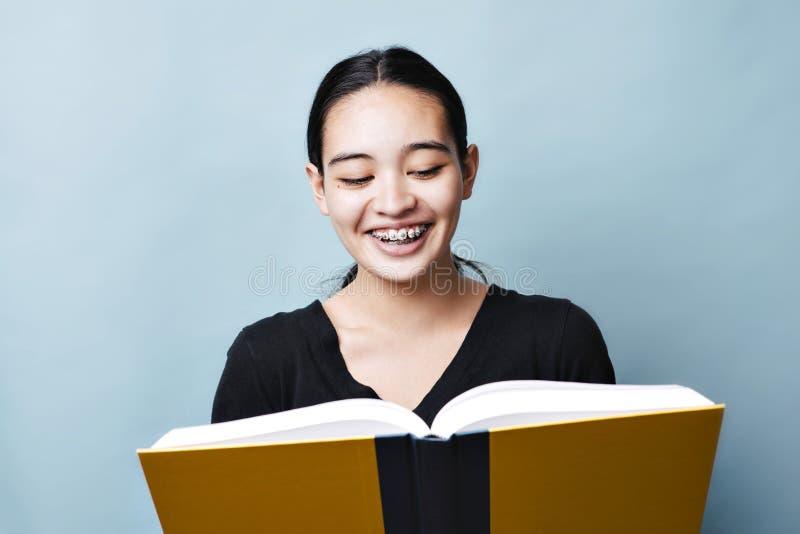 El adolescente joven lee en el libro de texto y sonríe expresión feliz de Lauging fotos de archivo