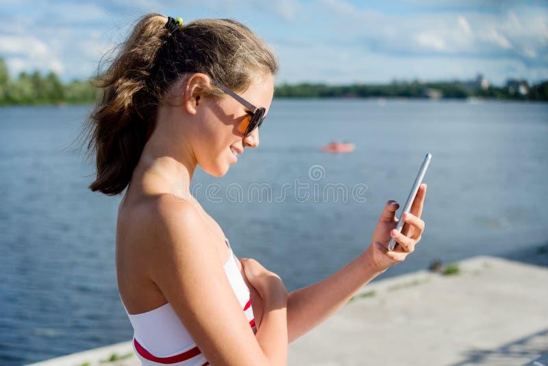 El adolescente joven tira el vídeo en un smartphone para su canal En un día de verano soleado, en el parque de la ciudad imagenes de archivo