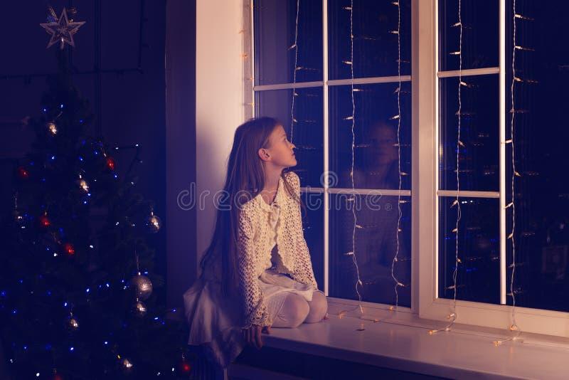 El adolescente lindo de la muchacha se sienta en un travesaño de la ventana, al lado de una Navidad tr fotografía de archivo libre de regalías