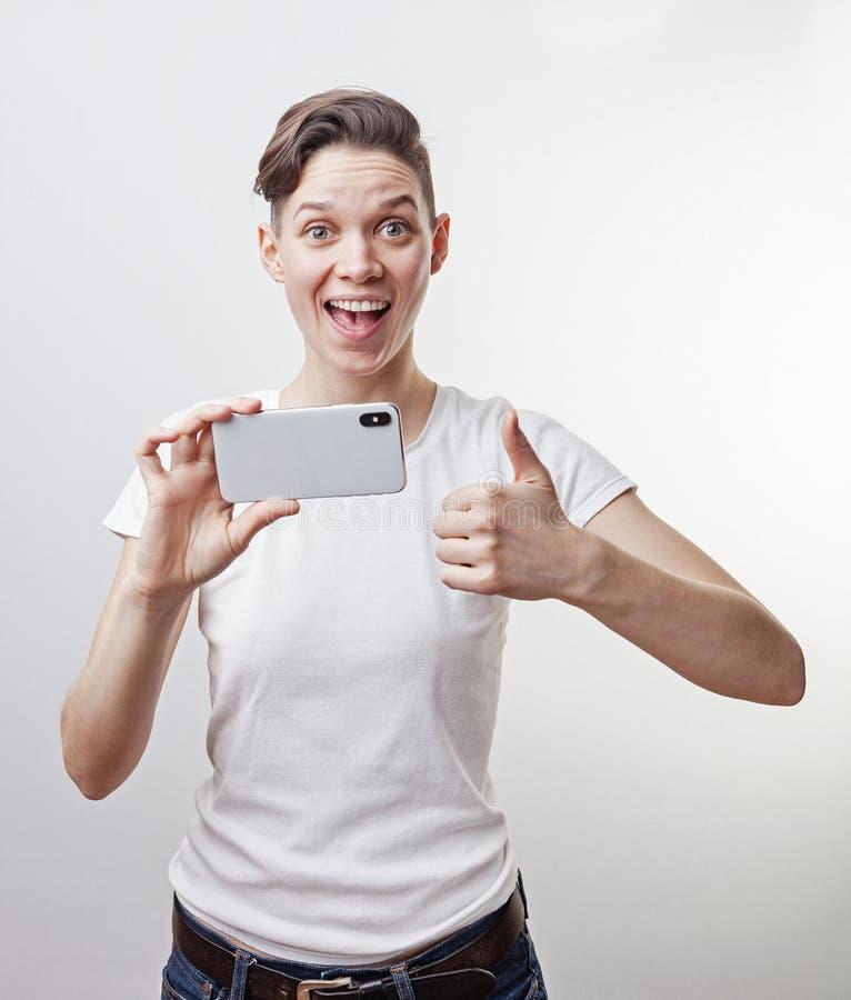 El adolescente magnífico está tomando una foto usando cámara delantera en su smartphone y está mostrando el pulgar para arriba Ai foto de archivo