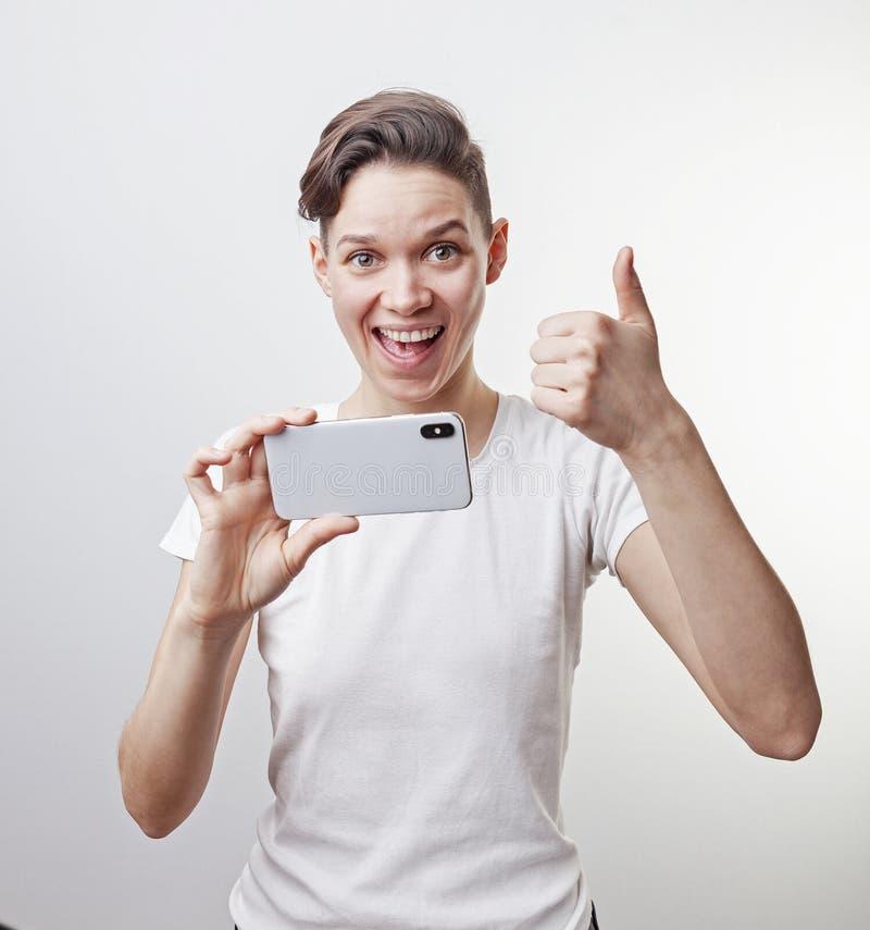 El adolescente magnífico está tomando una foto usando cámara delantera en su smartphone y está mostrando el pulgar para arriba Ai fotos de archivo libres de regalías