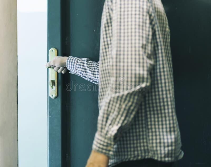 El adolescente masculino joven en la camisa a cuadros que se va a casa y cierra la puerta imagenes de archivo