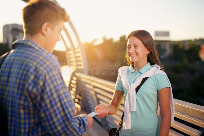 El adolescente que celebra los boletos para el cine, los da a la muchacha imagen de archivo