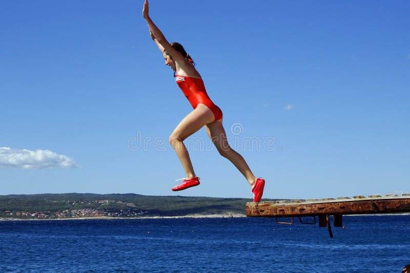 El adolescente que salta en el mar en el sol fotos de archivo libres de regalías