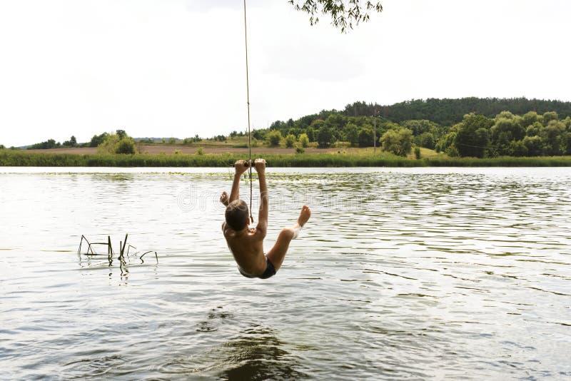 El adolescente que salta en el río de la cuerda de balanceo en día de verano soleado fotos de archivo