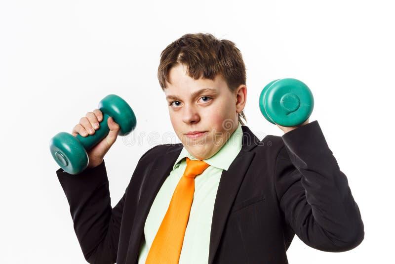 El adolescente se vistió en el traje de la oficina que hacía ejercicios del deporte foto de archivo libre de regalías