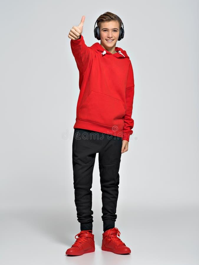 El adolescente se vistió en una sudadera con capucha roja y zapatillas de deporte de la calle imagen de archivo