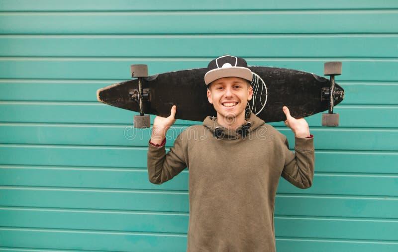 El adolescente sonriente en un casquillo y una sudadera con capucha se coloca en el fondo de una pared verde, sostiene un longboa fotografía de archivo