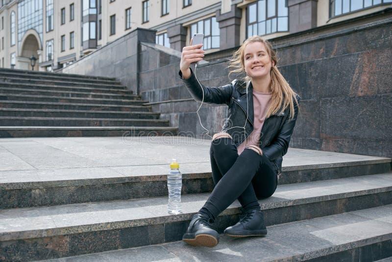 El adolescente sonriente joven de pelo largo elegante de la muchacha en una chaqueta de cuero y vaqueros rasgados hace un selfie fotografía de archivo libre de regalías